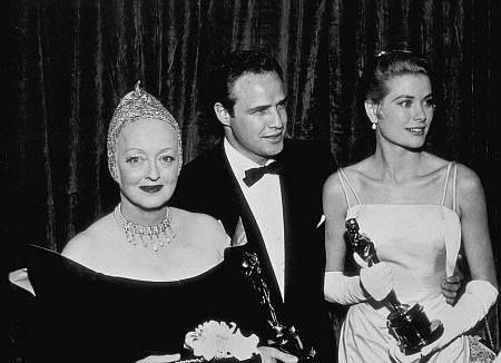 "BETTE DAVIS as a presenter at the 1955 Academy Awards, next to the best-actor-actress winners Marlon Brando and Grace Kelly. Her rather unique headgear can be explained by her at-the-time filming of ""The Virgin Queen,"" in which she appeared, once again, as the monarch Elizabeth I. Bette went so far as to have her head shaved for the role; hence her choice of Elizabethan-style headdress to wear at the Oscar ceremony."