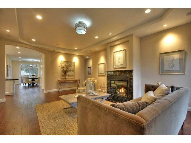 Living Room Fireplace With Stone Surround And Tray Ceiling CB