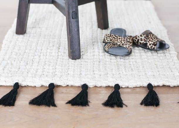 tassel fringe rug with animal print slippers and stool