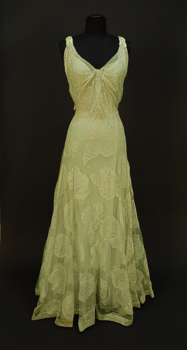 """WORTH NET EVENING GOWN with SEASHELL DESIGN, c. 1932. Sleeveless pale seafoam green V-neck decorated with large shells of various types, the straps with iridescent sequin decoration and scattered rhinestones at shoulder and down low back, attached seafoam crepe de chine slip, side closure. Label """"Worth"""""""