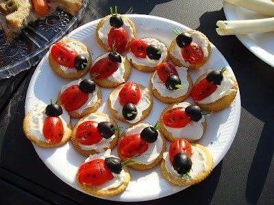 THESE SIMPLE LADYBUG SNACKS WERE MADE FROM RITZ CRACKERS SPREAD WITH CREAM CHEESE AND TOPPED WITH HALF OF A CHERRY TOMATO FOR THE BODY AND HALF OF AN OLIVE FOR THE HEAD. THE DOTS WERE BLACK FOOD COLORING AND THE ANTANEAS WERE GREEN ONION STEM SLIVERS.