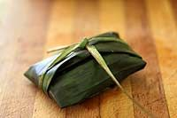 Banana leaf tamales recipe.  Tamale corn masa, stuffed with cheese, calabasitas squash, carrots, tomatoes, garlic, and chili sauce, wrapped in banana leaves and steamed. ~ SimplyRecipes.com