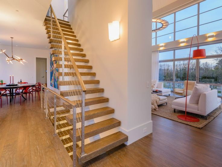A floating nautical style staircase with oak treads and steel and wire railings topped with a wooden handrail leads to the upper and lower levels.