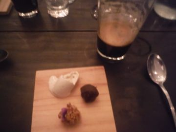 Seventh Course--White chocolate truffle, rolled in bacon and topped with a violet, accompanied by a dark chocolate truffle and a dollop of ice cream. Served with Brasserie Madera Imperial Stout.
