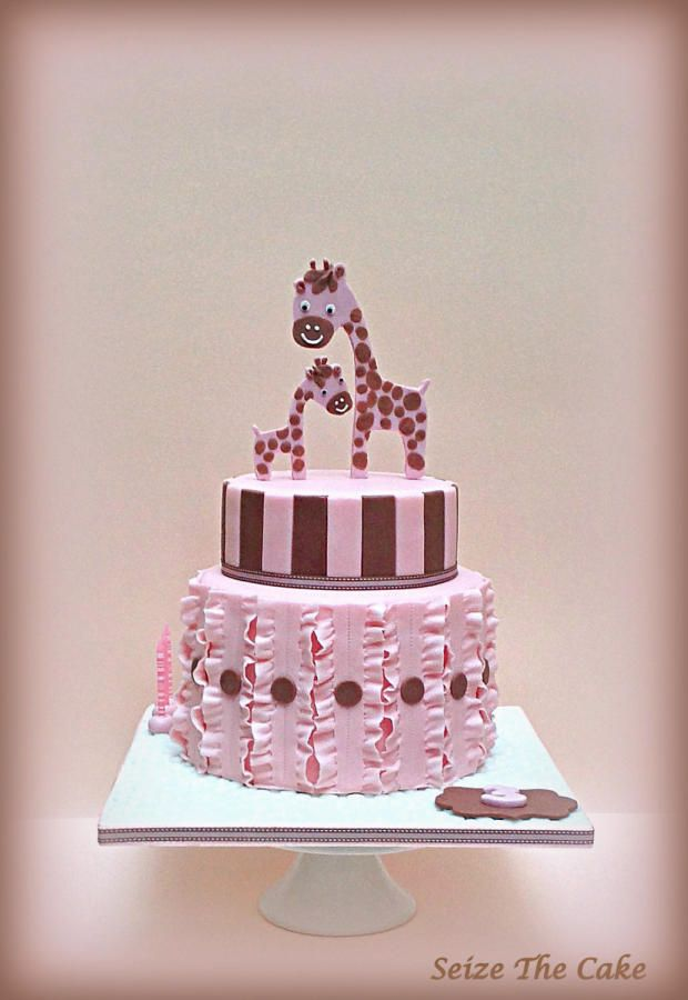 Chic and elegant two tier giraffe themed birthday cake with various decorative details such as fondant ruffles and stripes in pink and chocolate brown. Giraffe cake toppers (2D) totally handmade.