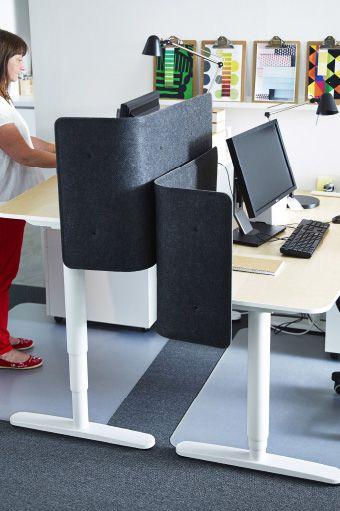 Deux bureaux réglables en hauteur placés l'un devant l'autre avec écrans de séparation gris