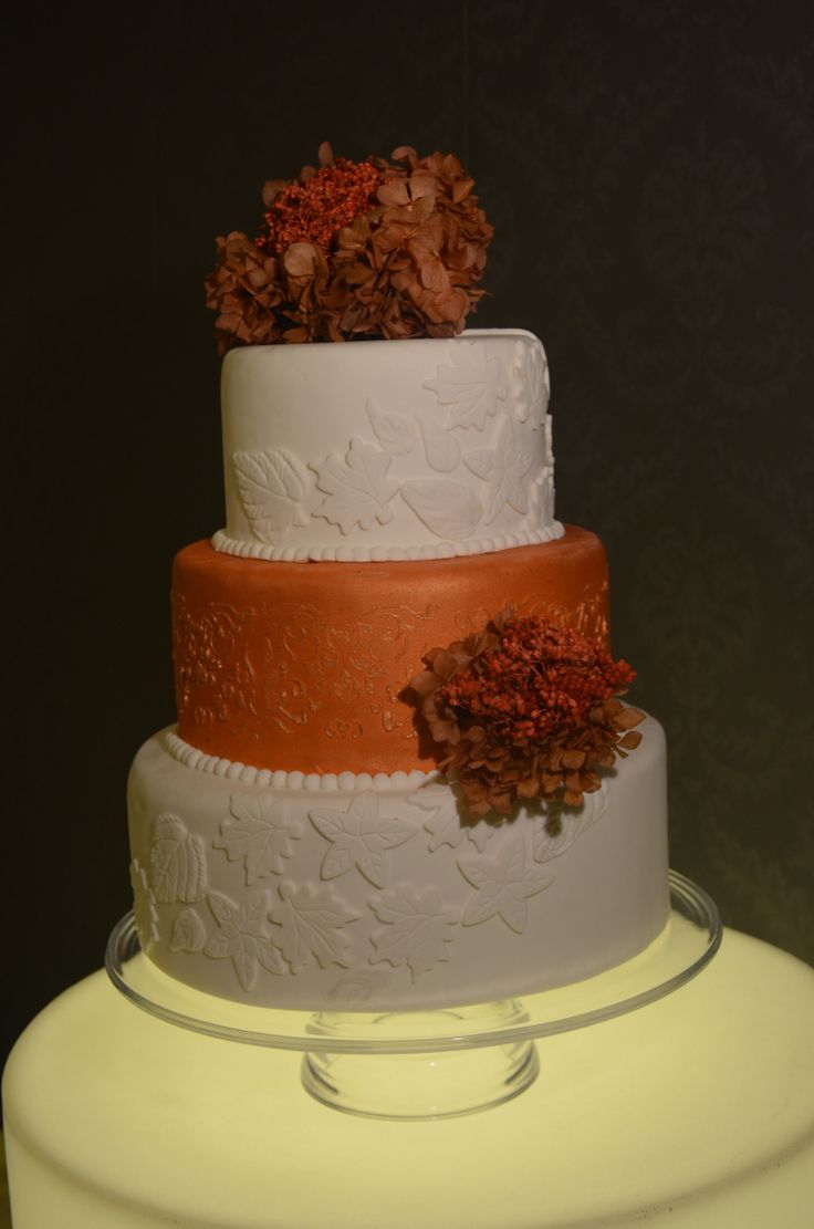 Fall Wedding Cake. Nico's Cakes otoño 2014; Torta de bodas diseñada para la temporada de otoño, utilizando el cobre como color característico de la estación, jugando con bouquets de flores secas a tono, alrededor, en el fondant distintos tipos de hojas simulan el correr del viento otoñal.