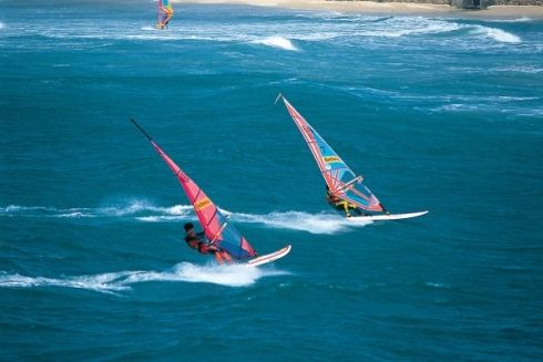 Gauteng Windsurfing - Feel the wind in your hair as you slice through the water on a Wind Surfing Adventure. Windsurfing or boardsailing is a sport that combines sailing and surfing. You can windsurf on a calm lake or in rough seas – as long as there is a breeze that you can catch in your sail. Windsurfers sail by standing on top of a windsurfing board (called the deck), controlling the sail using a rigid bar (called a boom).