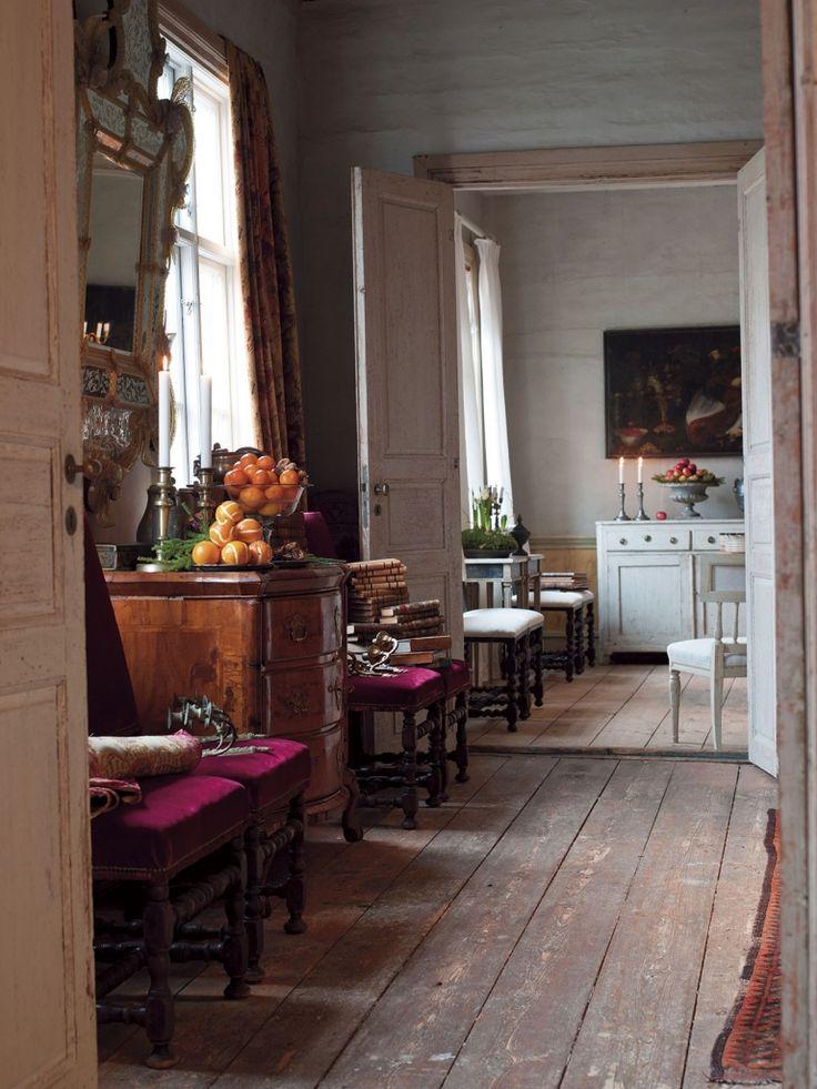 En gång mellan två rum med en byrå från barocken och två antika stolar.
