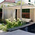 Ogród nowoczesny w Wilanowie z elementem wodnym i altaną z drewna klejonego.