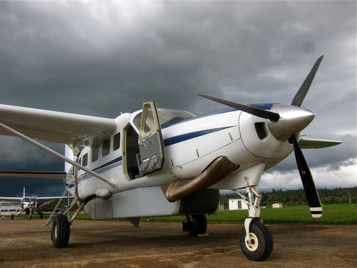 A photo of an AirServ Cessna C208B airplane in Gulu, Uganda (ICAO code HUGU). The aircraft registration is 5X-ASB