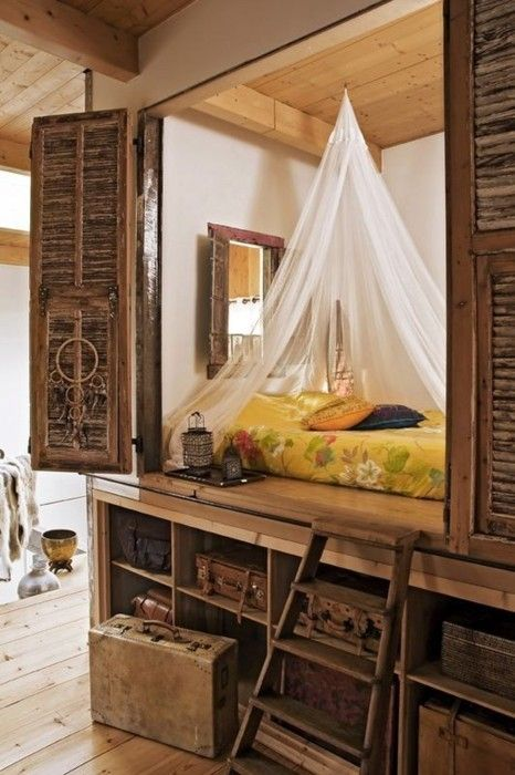 A dream of a built-in nook bed is concealed behind wooden shutters, and is draped with a net canopy for a softening touch. Cubbyholes under the bed platform provide extra storage.  The vintage well-traveled suitcases, canopy, and shutters also remind me of some exotic locale, like Casablanca