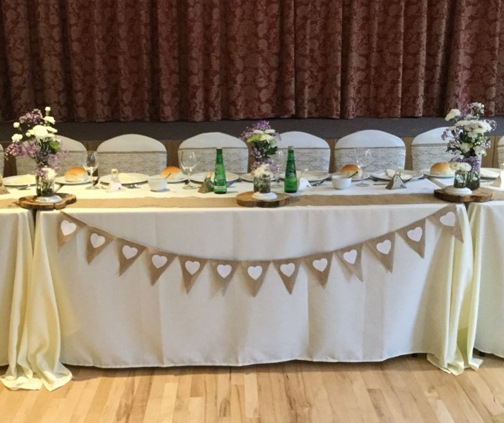 Rustic wedding with a top table decorated with Ivory table cloths, Ivory chair covers with hessian & lace sashes, hessian table runner small & medium sized jars filled with flowers complimented the rustic theme Available to hire from Eternally Yours Wedding & Prom Services, cv9 2dn