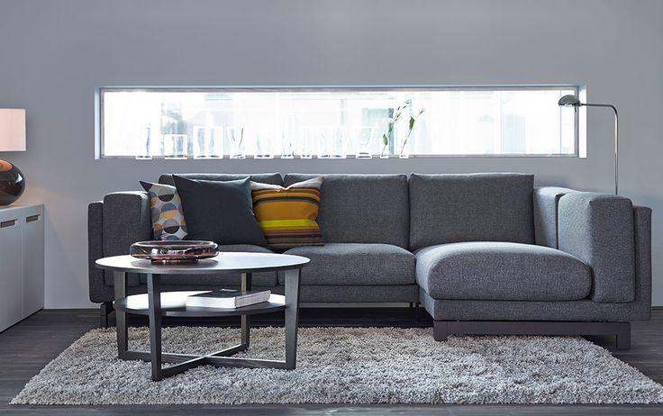 Pokój dzienny z sofą  2-osobową i szezlongiem z ciemnoszarym pokryciem oraz czarnobrązowym stolikiem kawowym