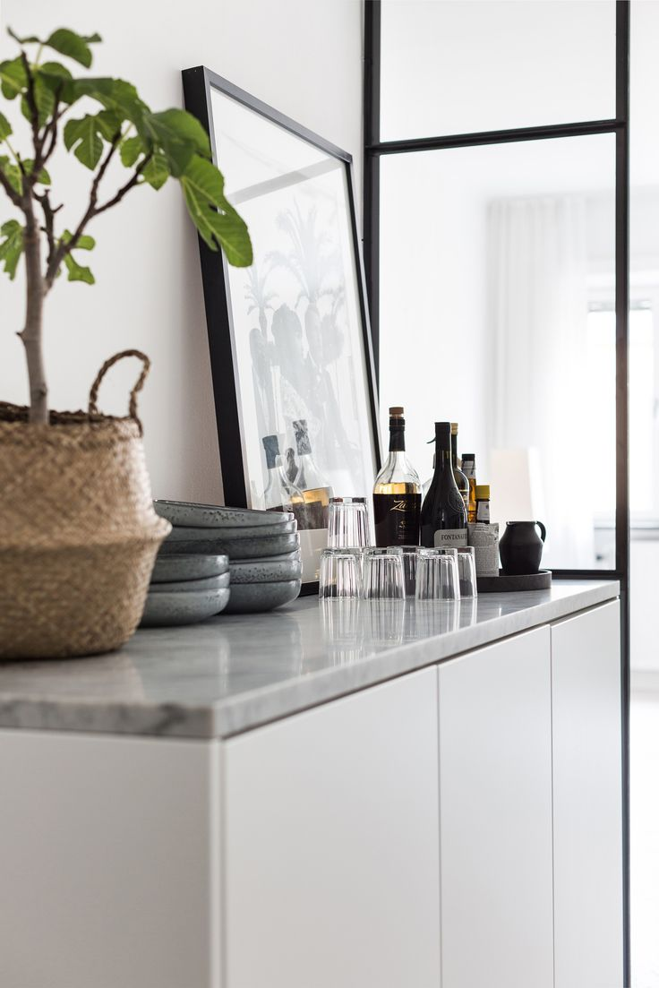 This would be great in either the kitchen or dining room. Love the marble shelf on top of the white unit. The stack of dishes and glasses look great with the artwork and seagrass basket with a small fig tree. Fantastic Frank