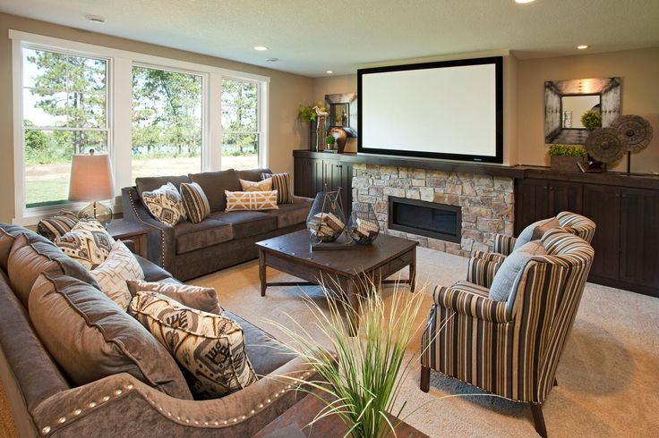 Lower level living space with large projector screen and built-in shelving alongside stone fireplace.