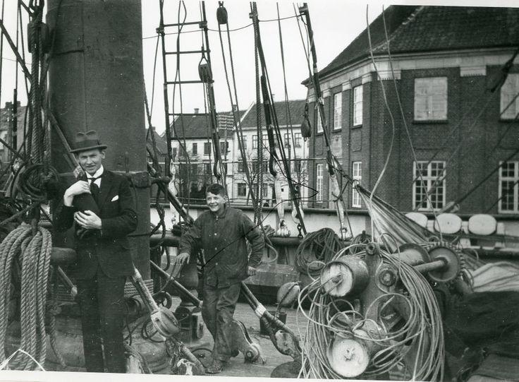 """Søren Berthelsen med hund om bord på den norske fuldrigger """"Maletta"""", Nakskov Havn 1919. Til højre ses en skibsdreng. Bygningen til højre er Nakskov Toldkammer."""