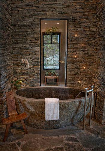 Estilo rústico creado con materiales de piedra tanto para pared como en la bañera y suelos, tonalidades oscuras