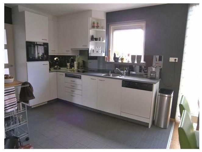 Semi-open keuken in een hoekopstelling, welke is voorzien van keramische kookplaat, afzuigkap, vaatwasser, koelkast en een combi-oven.