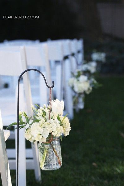 Decorate you shepherd hooks. Aisle liner with Shepard hooks and simple white flowers. Mason jars need to go.