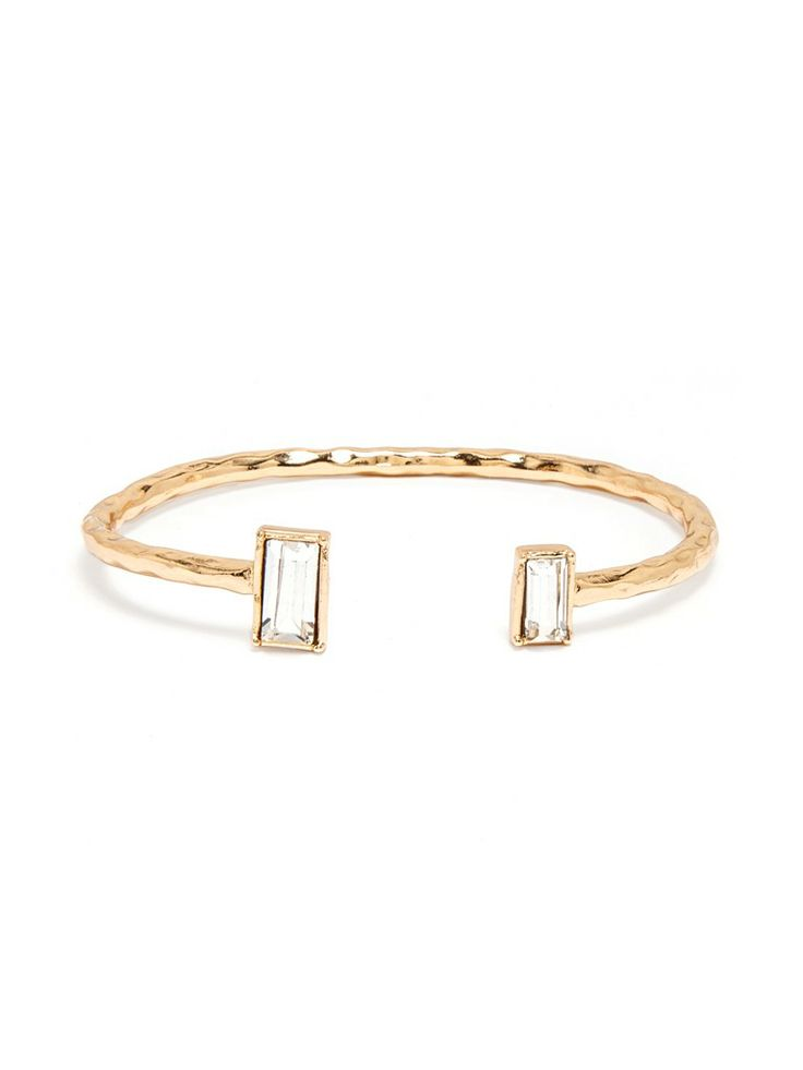 This modern twist on the solitaire gem is quite stunning; featuring two simple baguette crystals perched daintily on a wrapped gold cuff.
