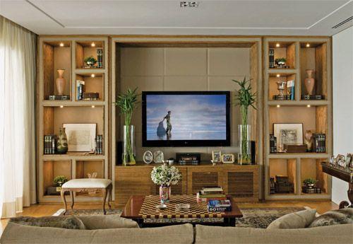 Estante de tv em madeira e couro bege + iluminação embutida nos nichos. Geralmente o tipo de luminária que se usa para embutir em marcenaria é a USA, que é mais baixa e não compromete a altura da prateleira. Projeto Débora Aguiar