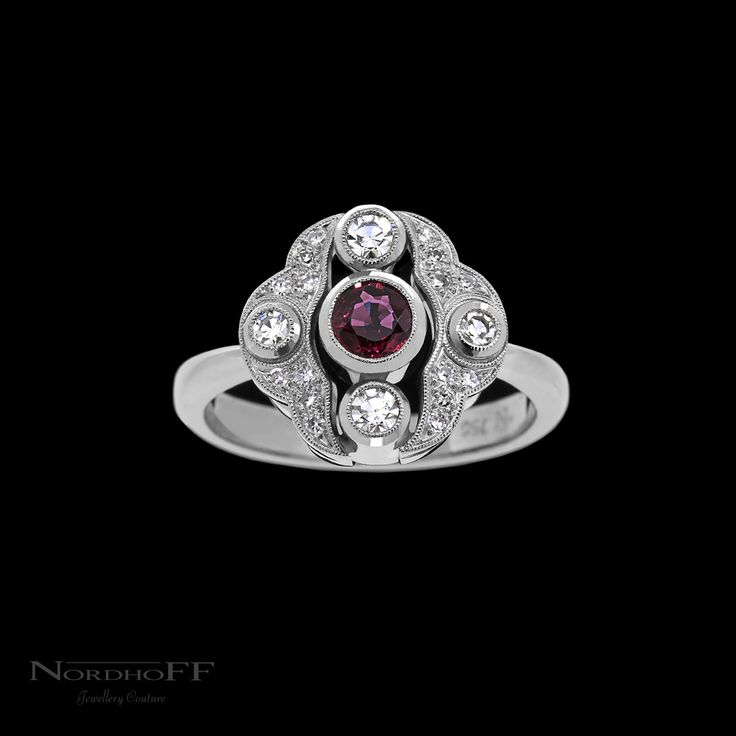 A romantic vintage style engagement ring needs a ruby as bright and lively as this one! Bezel set and finished off with fine milgrain the natural vivid red ruby is complimented perfectly by the unique sparkle of our top grade single cut diamonds. Memories of yesteryear are conjured up by the leafy diamond set details, and being all expertly hand made in 18k white gold, the traditional feel continues through the entire ring.