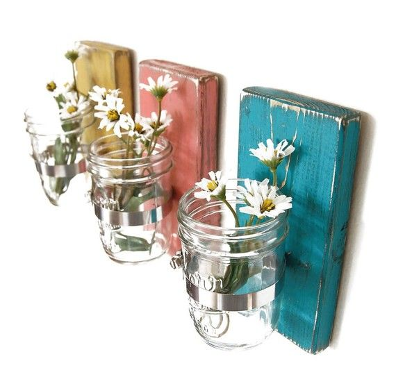 Clear mason jar flower holder sconces on painted wooden boards.