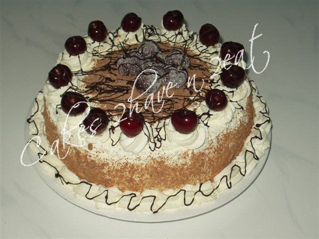 Black Forest cake topped with fresh cherries and drizzled chocolate.