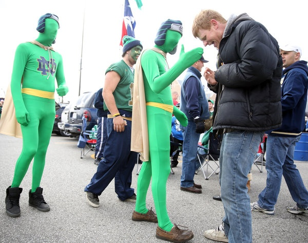 Men dressed in all green greet friends before the Notre Dame vs. Pitt football game