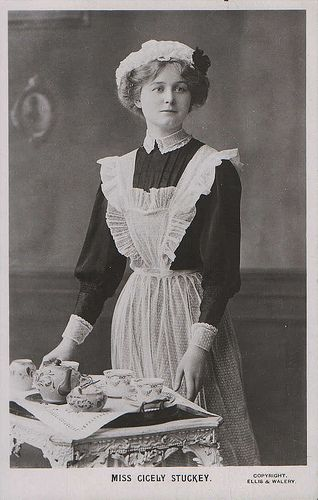 1900's - standing with perfect posture and an air of elegance herself - her hands delicately framing the tea tray - a BEAUTIFUL maid with a BEAUTIFUL tea tray