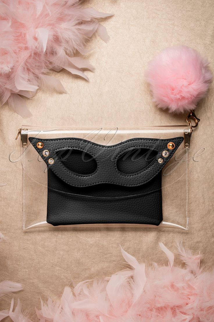 """With this 50s Mansfield Masquerade Clutch you will be the centre of attention... Mansfield style!The gorgeous black """"faux"""" leather spectacles are the eyecatcher of the transparent clutch and is inspired by the masquerade style eyewear of Paulette Guinet. Handmade from transparent plastic with beautiful details of gold toned metal, sparkling rhinestones and a pink puff ball charm made from fake fur... vavavoom! A real dream for all bag lovers! ;-)   Magn..."""