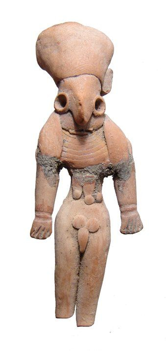 Mehrgarh terracotta male figure, Indus Valley Civilization, 3000-2500 B.C. Depicted standing nude with arms at his sides, wearing tall headdress with lappets over shoulders and a broad collar, his features are stylized with wide, round eyes and large nose, some scarification is apparent on his belly, 7.9 cm high. Private collection