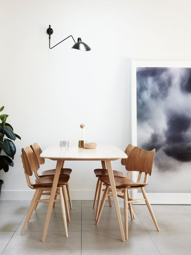 """House tour: a private home for one in inner-city Melbourne: """"The owner's lifestyle was analysed for the design... so she can enjoy the dining area alone, as well as with guests. We  added a Serge  Mouille wall light, and table lighting that gives a  textured effect and so much ambience."""" Ercol 'Windsor Plank' table and 'Butterfly' chairs from Temperature Design. Serge Mouille 'Applique 1 Bras Pivotant Courbe' wall lamp from Cult. 'Wednesdayfiveten2010' artwork by Trevor Mein from Otomys."""