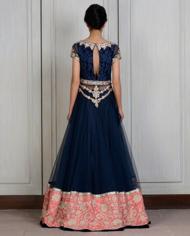 Top shirt of this Blue long jacket lehenga is made in net fabric with zardozi embroidered silk yoke. Bottom border is of contrasting orange heavily floral Tilla embroidered paner. Boat neck with slice