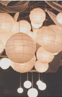 Various size lighted paper lanterns hanging from rafters at rustic wedding.