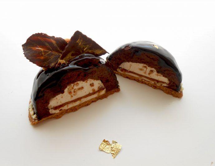 Semisfera di mousse alla crema biscotto con cuore di mousse ai pinoli su un croccante biscotto alle nocciole,ricoperto da glassa al cioccolato fondente