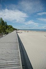 Wasaga Beach....warm shallow waters, hard packed sand, some times water like glass, with a good NW wind, surfable as well!