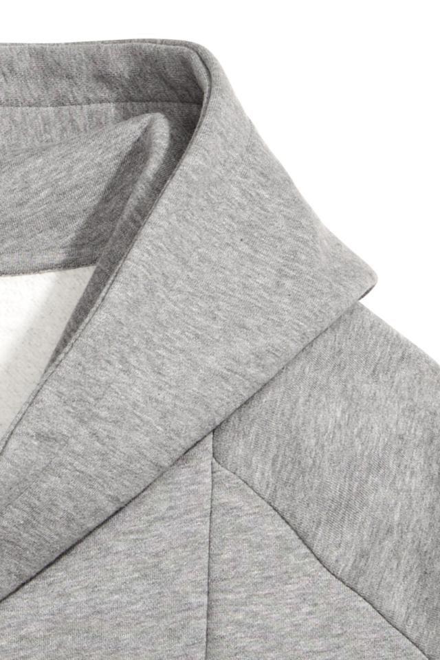 Cárdigan largo en tejido sudadera suave y jaspeado. Cuello esmoquin, capucha forrada y cremallera diagonal oculta. Bolsillos al bies y remate elástico en pu