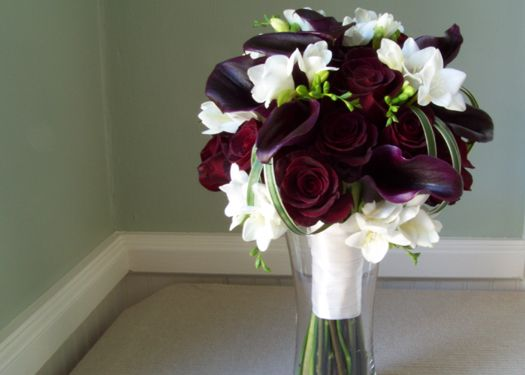 deep purple calla lilies, white freesias, wine-colored anemones, and looped variegated lily grass.