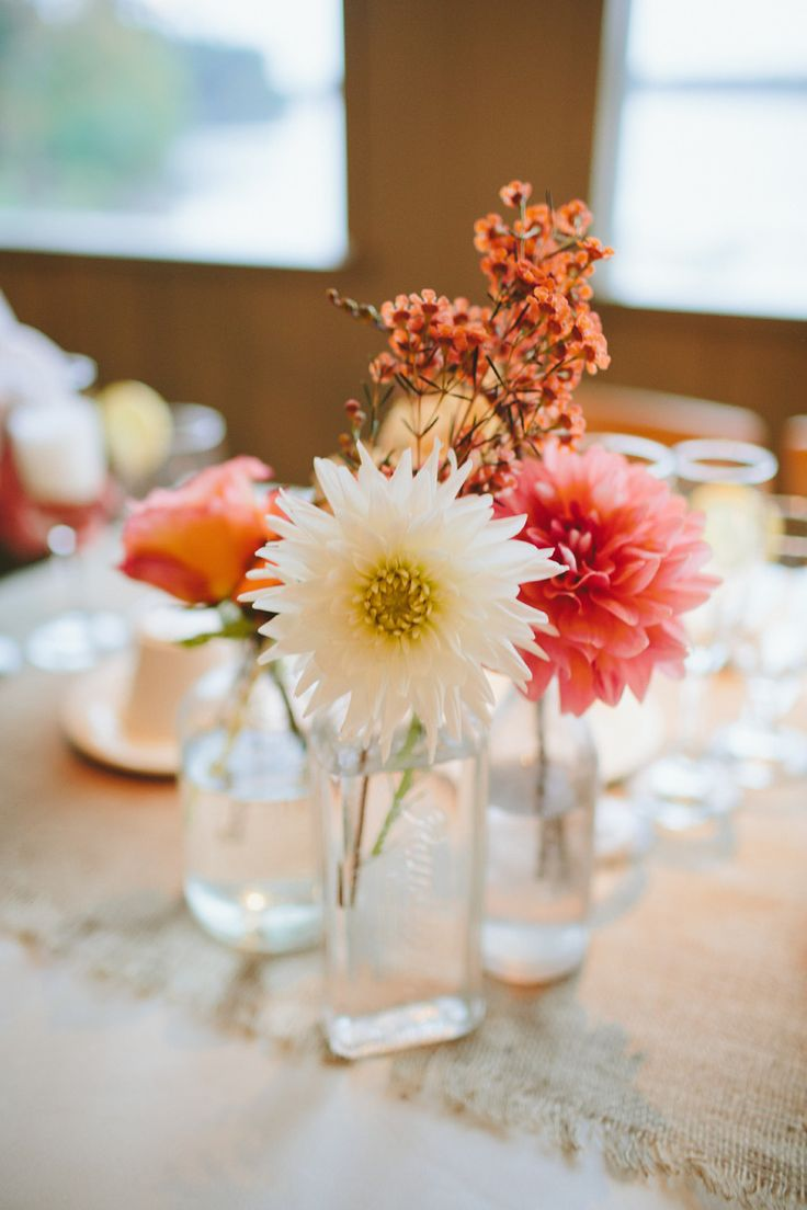 Posies -- Single blooms in eclectic containers. Love 'em! See more on #smp here: http://www.StyleMePretty.com/mid-atlantic-weddings/2014/04/14/lakeside-poconos-wedding-with-a-camp-vibe/ Photography: KatchSilva.com