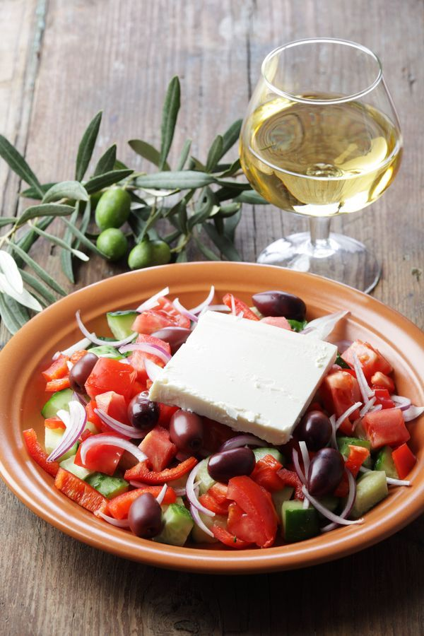 Greek salad consists of tomatoes, sliced cucumbers, onion, feta cheese, and olives (usually Kalamata olives), typically seasoned with salt and oregano, and dressed with olive oil. Sliced capsicum, usually green, is often added also.