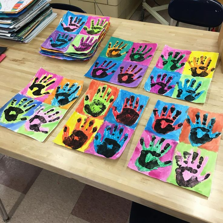 Crayon for first hand print, watercolor resist, black tempera for final hand print