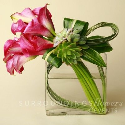 "Something small and modern in glass for the sweetheart table.  ""A modern flower arrangement of callas decorated with lily grass, aspidistra leaves and a cluster of beautiful succulents to add just the right touch. $150.00"""