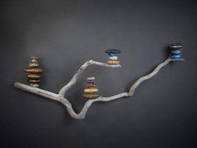 Polished rocks stacked and displayed on a branch.
