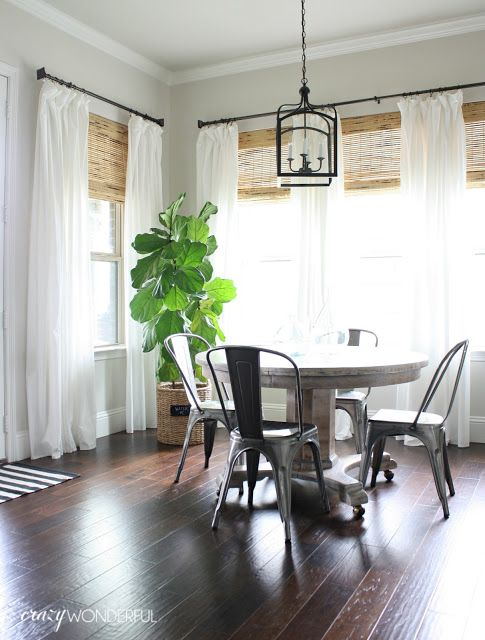 breakfast nook with white drapes metal chairs and a fiddle leaf fig