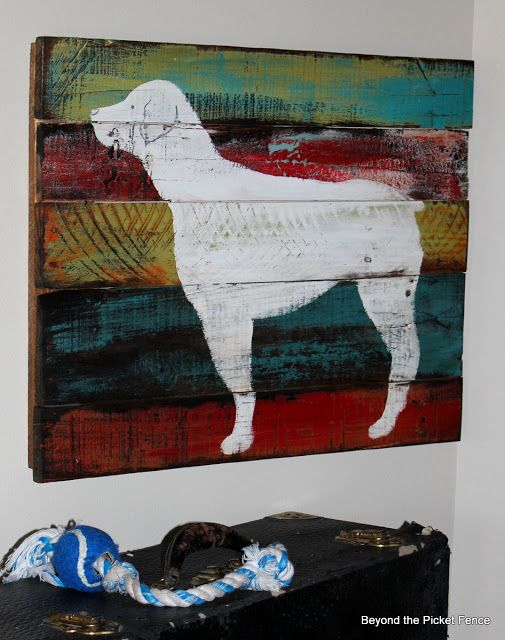 Beyond The Picket Fence a white, dog silhouette painted over the top of multi-colored scrap boards like a pallet. #woodscraps