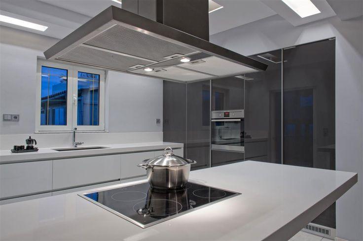 Μοντέρνα κουζίνα χωρίς πόμολα, με βαγονέτα με ενσωματωμένες χούφτες από λευκό ακρυλικό, ντουλάπια από ανθρακί τζάμι και κεντρική νησίδα με εστίες.