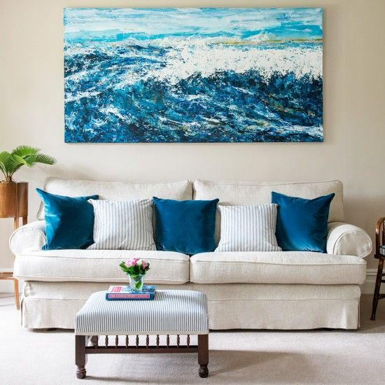 Add colour to a neutral living room with a bold piece of art and some accompanying cushions - simple and so effective