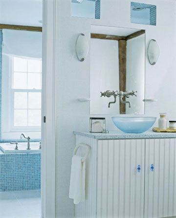 Light blue basin and tub in background surrounded by blue and white gives ocean & island feel